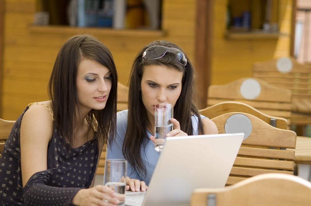 Due ragazze che consultano Internet attraverso il proprio laptop.
