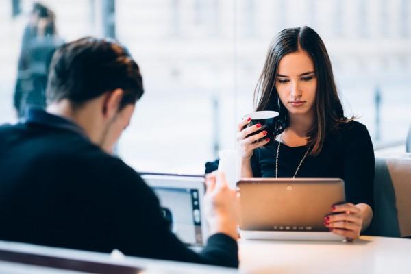 Un uomo e una donna seduti in un bar navigano su Internet usando il wifi con i propri dispositivi.