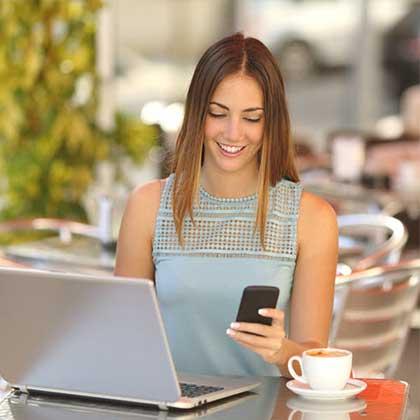 Donna consulta il suo smartphone seduta al tavolino di un bar.