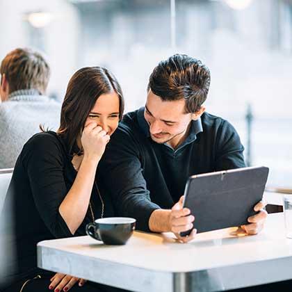 Uomo e donna seduti in un bar ridono mentre consultano un tablet connesso all'hotspot wifi del locale.