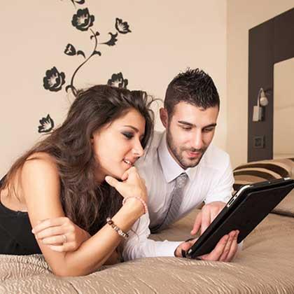 Una coppia stesa sul letto di un hotel consulta Internet su un tablet connesso al wifi della camera.