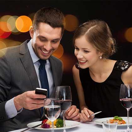 Una coppia seduta al tavolo di un ristorante ride mentre consulta uno smartphone.