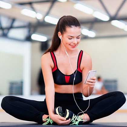 Una donna che fa stretching mentra consulta il suo smartphone connesso a un wifi hotspot.