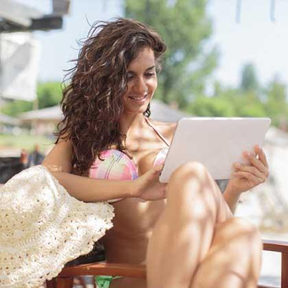 Una donna seduta su una sdraio da spiaggia naviga su Internet con il suo tablet connesso al wi-fi dello stabilimento balneare.