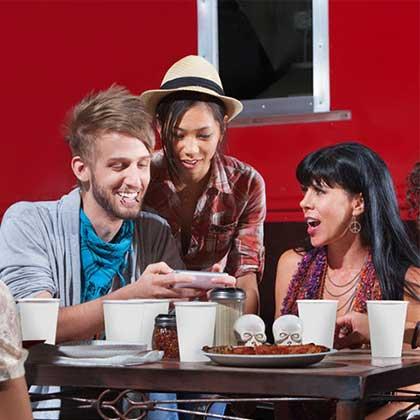 Un gruppo di amici consulta uno smartphone all'interno di un pub.