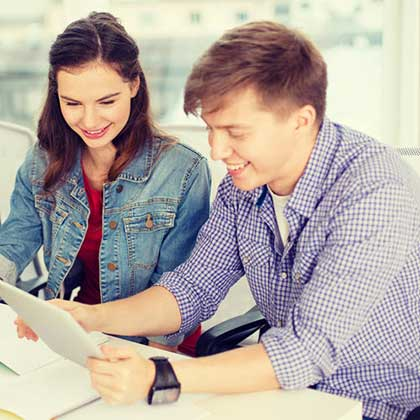 Una coppia seduta in uno studio si diverte navigando su Internet con uno smartphone.