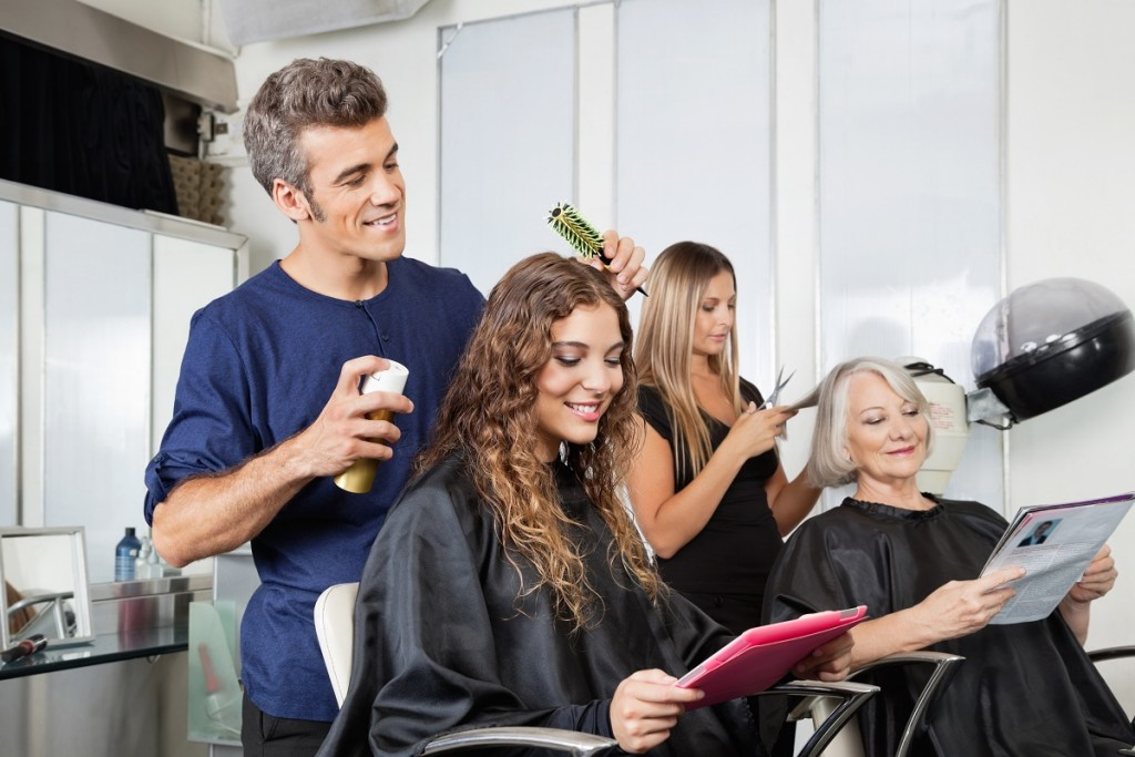 Una donna seduta dal parrucchiere con sulta il suo tablet connesso a Internet in WiFi, mentre il parrucchiere le sistema i capelli.