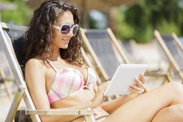 Donna su sdraio che naviga su Internet in Wi-Fi usando un tablet in spiaggia .