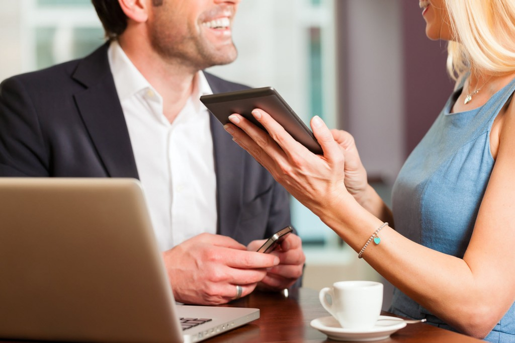Un uomo e una donna che consultano tablet e pc durante una conversazione al bar