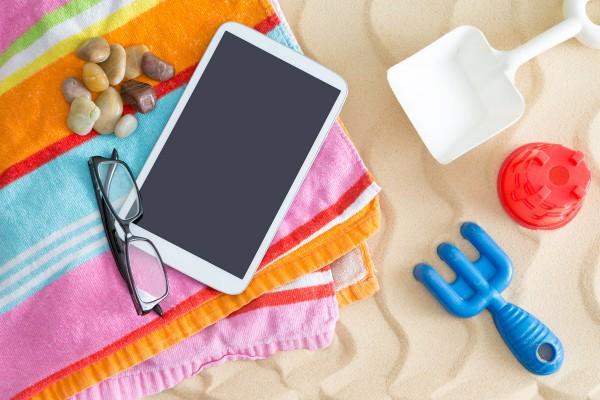 Telo da spiaggia steso sulla sabbia con sopra diversi oggetti, tra cui un tablet e degli occhiali.