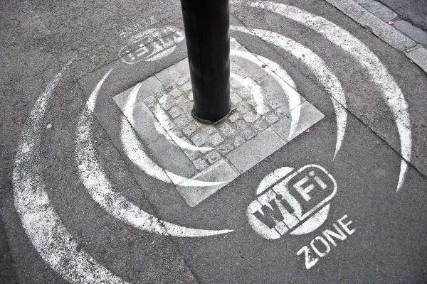 Strada con un segnale orizzontale che dichiara la peesenza di un zona di wi-fi pubblico.