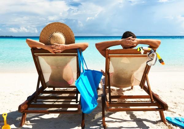 Uomo e donna stesi su sdraio in spiaggia, visti da dietro.