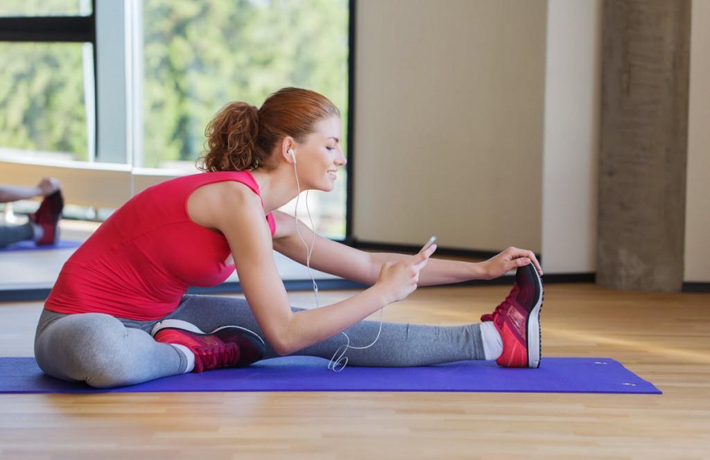 Donna che fa stretching in palestra mentre consulta il suo smartphone.
