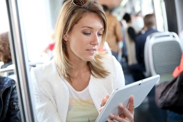 Donna che consulta un tablet su un mezzo pubblico.
