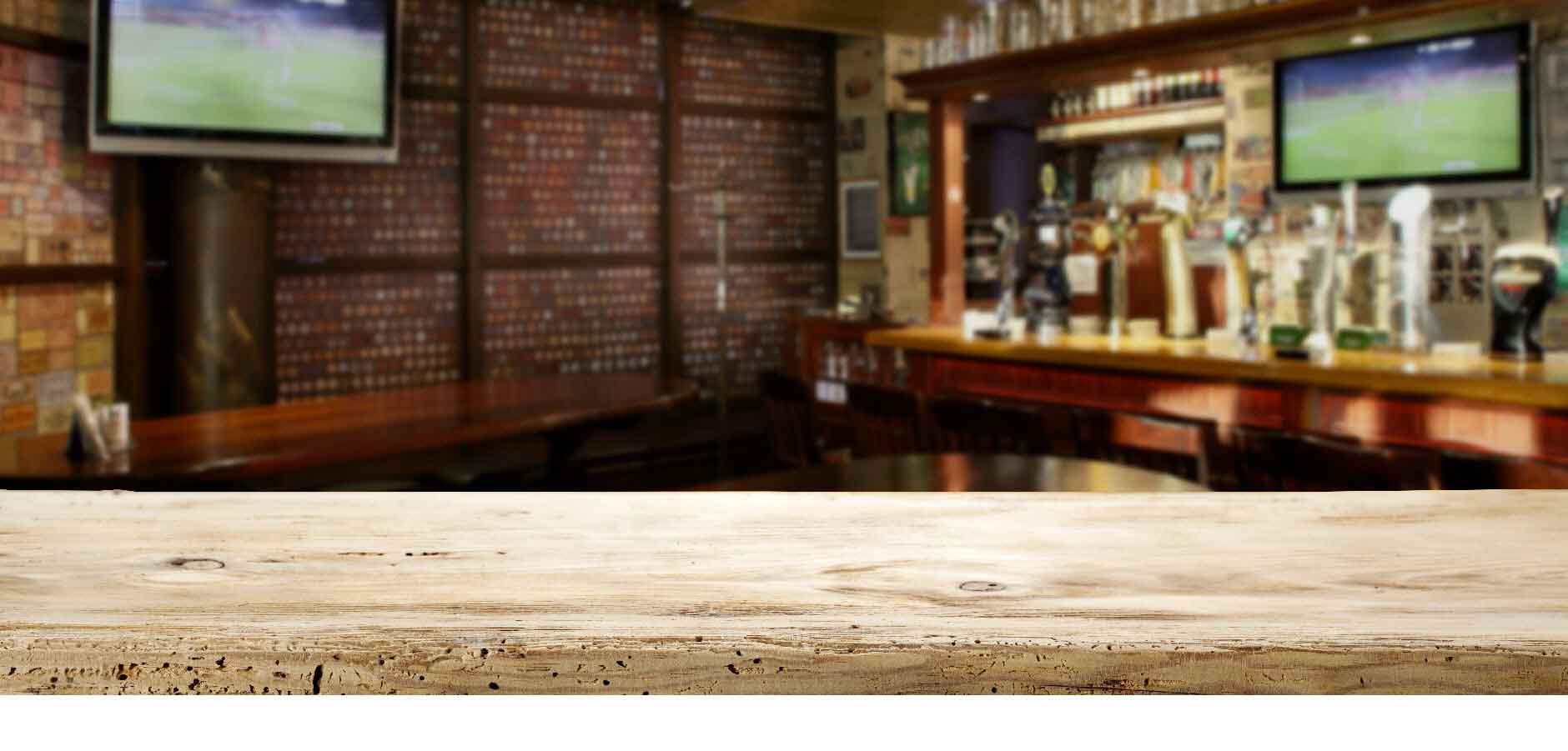 Bancone in legno con il bancone di un bar, con sopra bottiglie di vario tipo, e due schermi tv appesi alle pareti sullo sfondo.